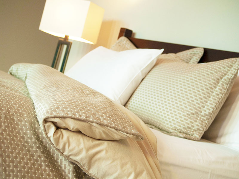 Image of a bed made with pillows.